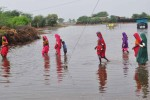 Pakistani people leave a flooded area following monsoon rains in Badin on August 12, 2011. Devastating rains in Pakistan killed at least 21 people overnight, destroying crops and houses in the flood-prone south of the country, a government official said. Last year, the worst floods in Pakistani history affected 21 million people and killed another 1,750. Charities accuse Pakistan of since failing to invest in prevention measures.  AFP PHOTO/ Yousuf NAGORI