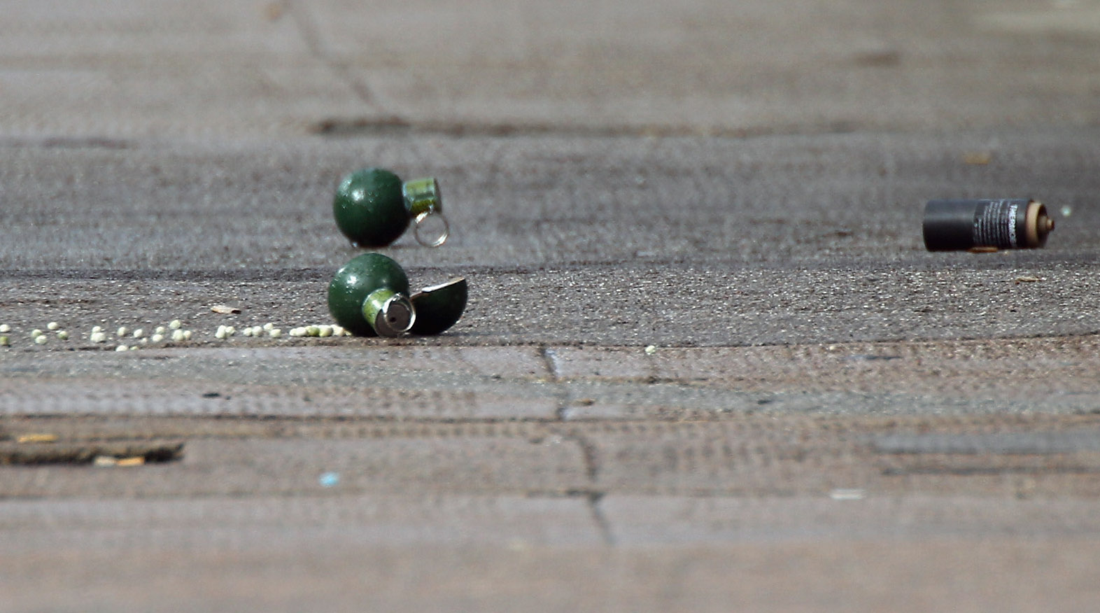 GLASGOW, SCOTLAND - SEPTEMBER 10:  Grenades lay on a pavement on Dumbarton Road during an ongoing incident on September 10, 2010 in Glasgow, Scotland. Armed response units were called to a property in the West End following reports of grenades being thrown from a tenement flat. A man has barricaded himself inside the flat following a domestic disturbance.  (Photo by Jeff J Mitchell/Getty Images)