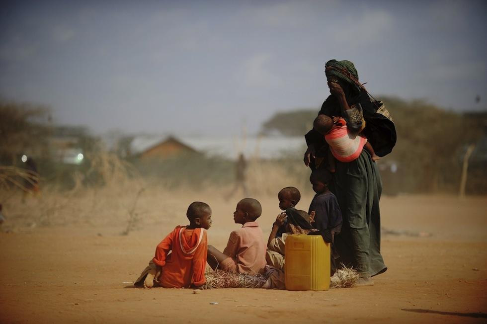 """Sarura Ali (R) covers her eyes from wind blown dust as she stands with her six children outside a food distribution point in the Dadaab refugee camp in northeastern Kenya on July 5, 2011. Sarura, her husband and their children arrived at the camp early on July 5 after having trekked for eight days from their home in Sakow, Somalia.  Dadaab, a complex of three settlements, is the world's largest refugee camp. Built to house 90,000 people and home to more than four times that number, it was already well over its maximum capacity before an influx of 30,000 refugees in June. Upon arrival, the refugees find themselves tackling a chaotic system that sees new arrivals go days, even weeks, without food aid. """"It still takes too much time for refugees to get proper assistance,"""" Antoine Froidevaux, Medecins Sans Frontieres's (Doctors Without Borders) field coordinator in Dadaab told AFP. """"The answer in terms of humanitarian aid is not satisfactory at all at the moment.""""          AFP PHOTO/Roberto SCHMIDT (Photo credit should read ROBERTO SCHMIDT/AFP/Getty Images)"""