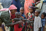 A government soldier on patrol in the streets of Somalia's war-torn capital demonstrates to Somali children how to use a Kalashnikov rifle during a gesture by the soldiers to win the goodwill of the residents of Mogadishu, on September 13, 2009. British intelligence chiefs have warned Prime Minster Gordon Brown's government that the number of young Britons travelling to Somalia to partcipate in terror-training camps is rising noting that the number of people with no direct family connection in Somalia travelling there per year had quadrupled to 100 since 2004. The Shebab, an Al-Qaeda inspired movement, is spearheading a three-month-old offensive to topple Somalia's President Sharif Sheikh Ahmed and has imposed strict Sharia law in areas under its control. AFP PHOTO/ MOHAMED DAHIR (Photo credit should read MOHAMED DAHIR/AFP/Getty Images)