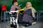 An Afghan woman listens to her physically handicapped child during a physiotherapy session at the ICRC Ali Abad Orthopaedic centre in Kabul November 12, 2009. REUTERS/Jerry Lampen