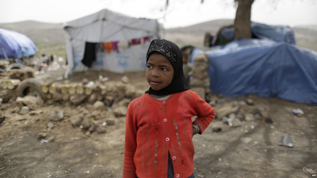 A displaced girl stands outside her family's hut at a camp for internally displaced people in the outskirts of Sanaa, Yemen, Friday, May 27, 2016. Yemen's conflict pits the government, backed by the Saudi-led coalition, against Shiite rebels known as Houthis allied with a former president. Yemen's war has killed at least 6,200 civilians and injured tens of thousands of Yemenis, and 2.4 million people have been displaced, according to U.N. figures. (AP Photo/Hani Mohammed)