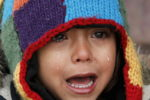 A child cries from the cold at a registration camp for migrants in Presevo, Serbia, January 17, 2016. REUTERS/Marko Djurica - RTX22QZU