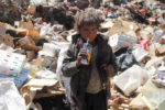 A boy drinks  expired juice on a pile of rubbish at landfill site on the outskirts of Sanaa, Yemen November 16, 2016. REUTERS/Mohamed al-Sayaghi - RTX2TZRP