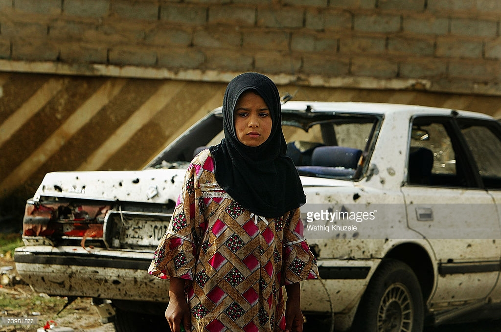 BAGHDAD, IRAQ – APRIL 26:  An Iraqi girl stands next to a car damaged in a car bomb explosion April 26, 2007 in Jadriya district in Baghdad, Iraq. The blast killed six people and wounded 18.  (Photo by Wathiq Khuzaie/Getty Images )