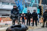 TOPSHOT - Bomb disposal expert Adam Roberts (L) rests his foot on a defused US-made bomb dropped during World War II a day after it was discovered on a harbourfront construction site in the Wan Chai district of Hong Kong on February 1, 2018.    A wartime bomb was defused in Hong Kong on February 1 after a busy commercial district went into lockdown, with roads closed and thousands evacuated from surrounding shops, hotels and offices.   / AFP PHOTO / Anthony WALLACE        (Photo credit should read ANTHONY WALLACE/AFP/Getty Images)