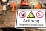 """Ein Warnschild """"Achtung Kampfmittelbeseitigung"""" steht am Sonntag (04.12.2005) in den frühen Morgenstunden auf einem Gelände am Klushügel an der Buerschen Straße in Osnabrück. Der Kampfmittelbeseitigungsdienst entschärft an dieser Stelle eine Fünf-Zentner-Bombe aus dem Zweiten Weltkrieg. Rund 4000 Menschen in einem Radius von 500 Metern wurden evakuiert. Foto: Friso Gentsch dpa/lni +++(c) dpa - Bildfunk+++   Verwendung weltweit"""